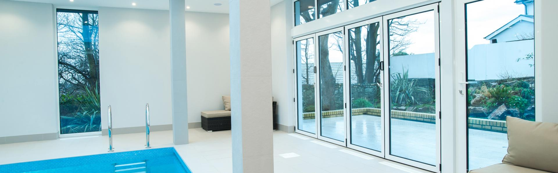 Aluminium bi fold doors by a swimming pool